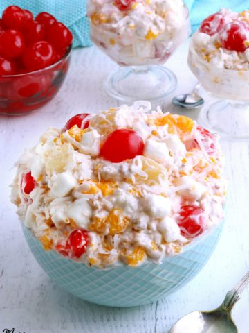 ambrosia salad in a bowl with cherries and two servings in the background
