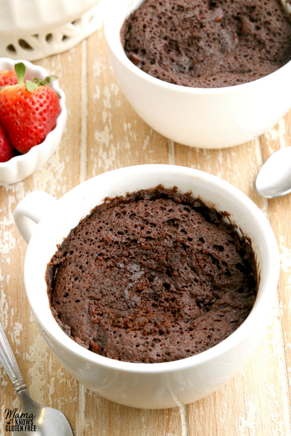 two gluten-free chocolate mug cakes with strawberries in the background