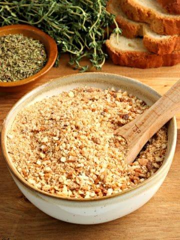 gluten-free bread crumbs in a bowl with a spoon and bread and herbs in the background