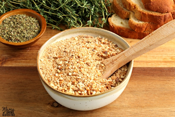 gluten-free bread crumbs in a white bowl with a wooden spoon with herbs and bread slices in the background