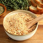 gluten-free bread crumbs in a bowl with a wooden spoon with bread and herbs in the background