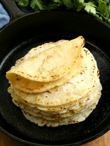 gluten-free tortillas in a cast iron pan with cilantro in the background