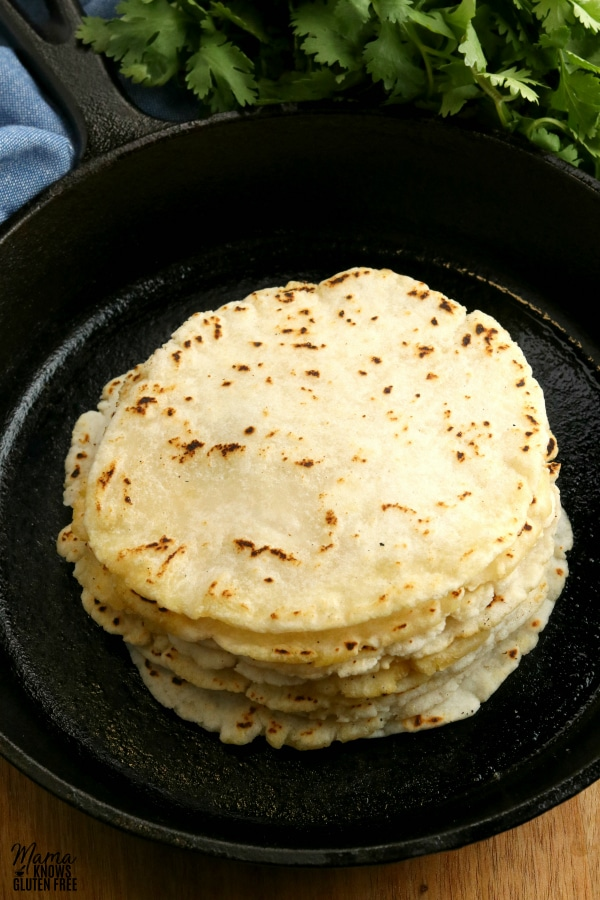 gluten-free tortillas stacked in a cast iron pan with cilantro in the backgorund