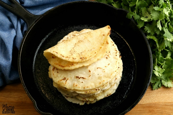 gluten-free tortillas stacked on top of eachother with one floded in a cast iron pan with cilantro and blue kitchen towel in the background