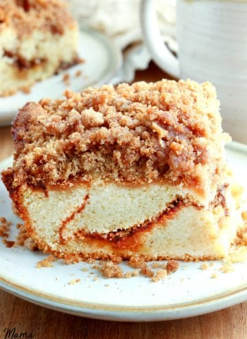 gluten-free coffee cake on a white plate with another slice and coffee in the background