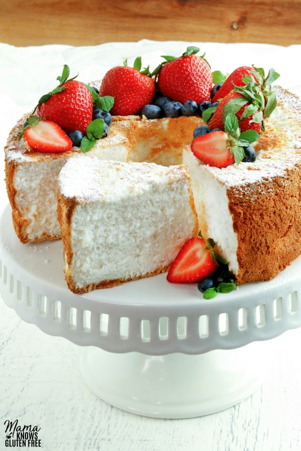 gluten-free angel food cake on a cake stand topped with berries