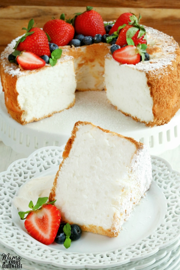 gluten-free angel food cake slice on a white plate with the cake in the background