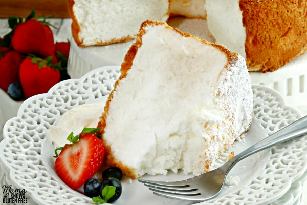 slice of gluten-free angel food cake on a white plate with berries and cream with the cake in the background