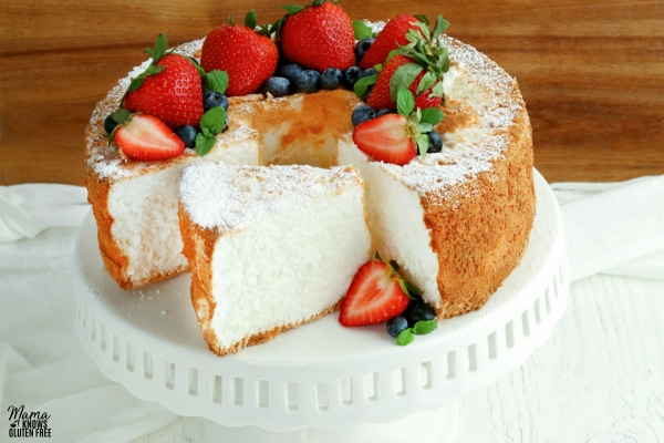 gluten-free angel food cake topped with fresh berries on a cake stand