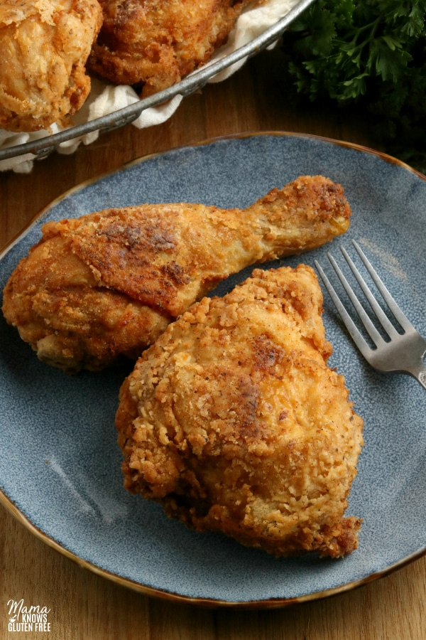 2 pieces of gluten-free fried chicken on a blue plate with a fork with more chicken in the background