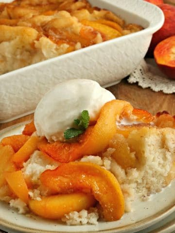gluten-free peach cobbler with ice cream on a plate with the cobbler in the background