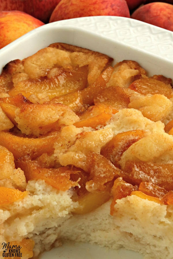 baking dish of gluten-free peach cobbler with slice cut out