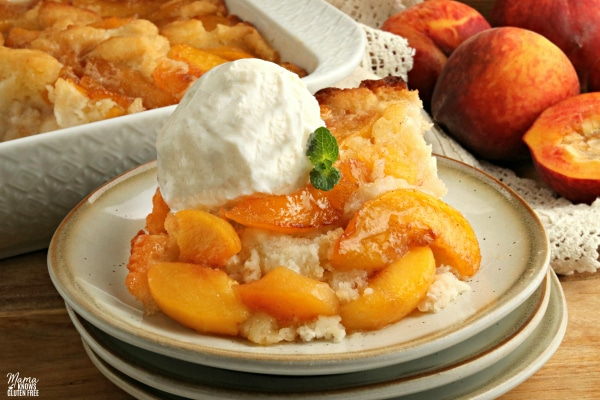 gluten-free peach cobbler with vanilla ice cream on a plate with the cobbler in the background