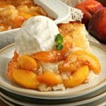 gluten-free peach cobbler topped with vanilla ice cream on a plate with the cobbler and peaches in the background
