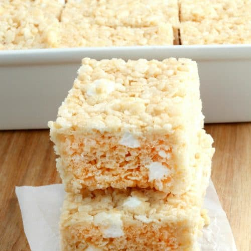 gluten-free rice krispies treats stacked on top of each other with the pan in the background