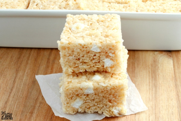 two gluten-free rice krispies treats stacked on top of each other with the pan of treats in the background