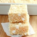 2 gluten-free rice krispies treats stacked with the pan of treats in the background