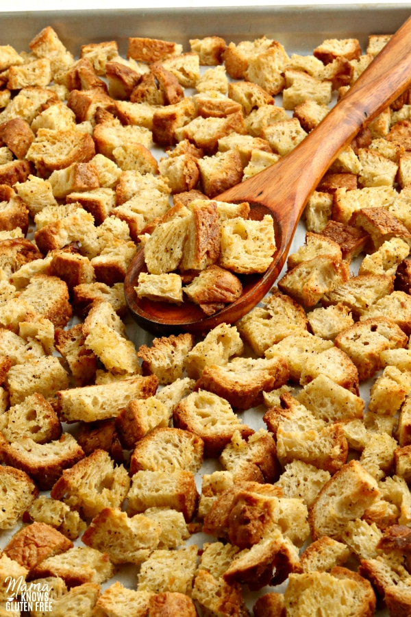 gluten-free crouotns on a baking sheet with a wooden spoon