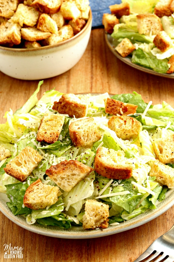 gluten-free croutons on a Caesar salad with a bowl of croutons in the background