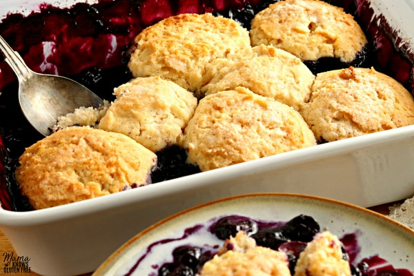 gluten-free blueberry cobbler in a white baking dish with a spoon and a serving on a plate