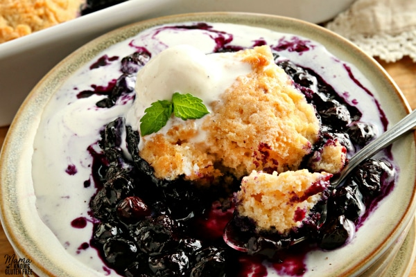 gluten-free bluberry cobbler serving with ice cream on a plate with a spoon