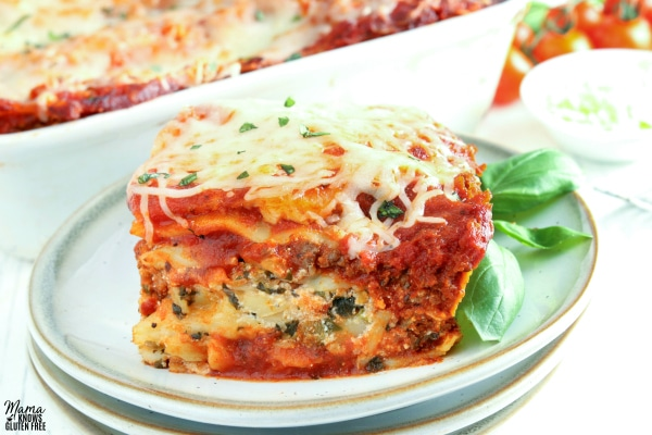 gluten-free lasagna slice on a plate with the pan of lasagna in the background