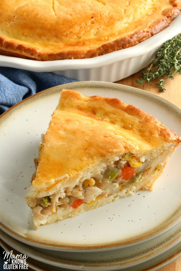 slice of gluten-free chicken pot pie on a plate with the pie in the background