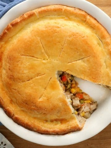 gluten-free chicken pot pie with slice cut out of it with blue napkin and pie cutter