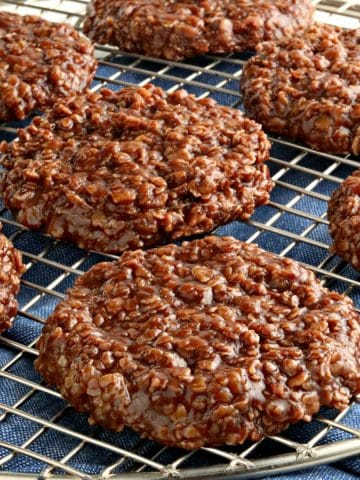 gluten-free no-bake cookies on a cooling rack with a blue kitchen towel underneath