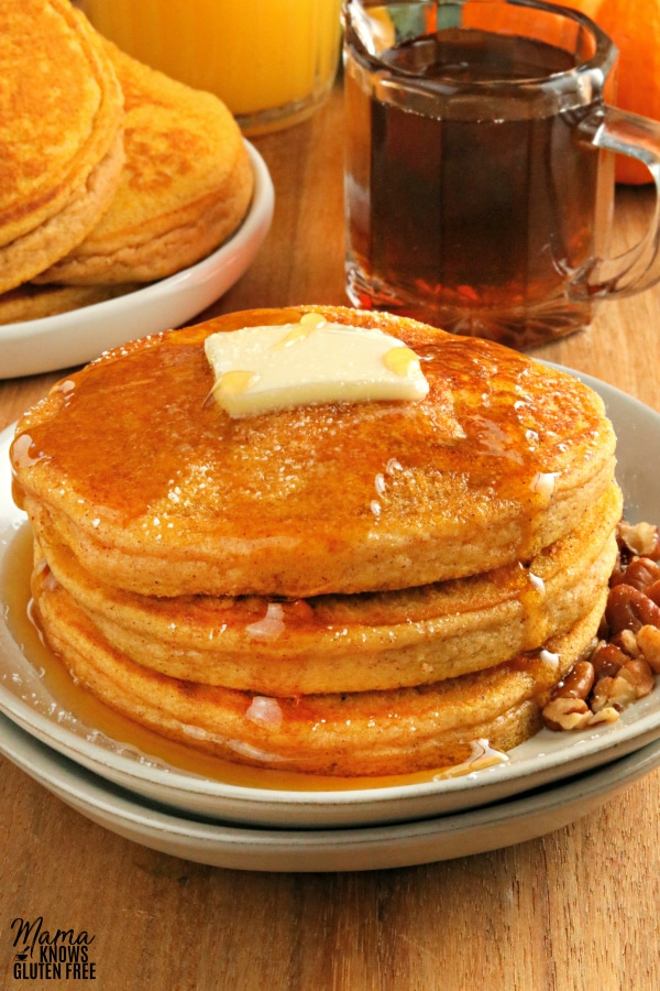 gluten-free pumpkin pancakes stacked on a white plate with syrup and more pancakes in the background