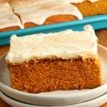 gluten-free pumpkin bars with cream cheese frosting on a white plate with the pan of bars in the background