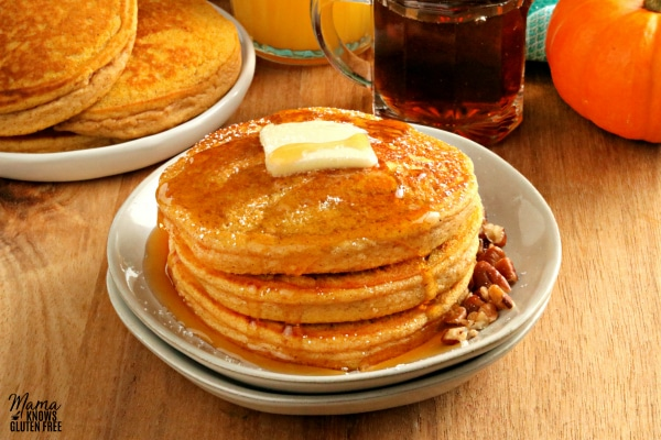 gluten-free pumpkin pancakes on a white plate with butter and syrup and more pancakes and syrup in the background