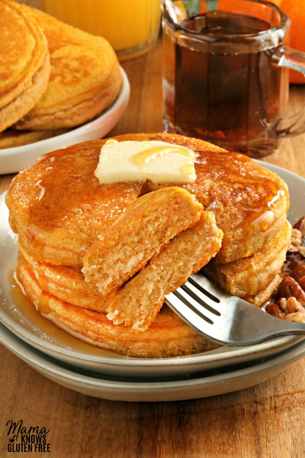 gluten-free pancakes with a bite on a fork with more pancakes and syrup in the backgorund.