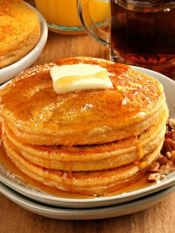 gluten-free pumpkin pancakes topped with butter and syrup on a white plate with more pancakes and syrup in the background