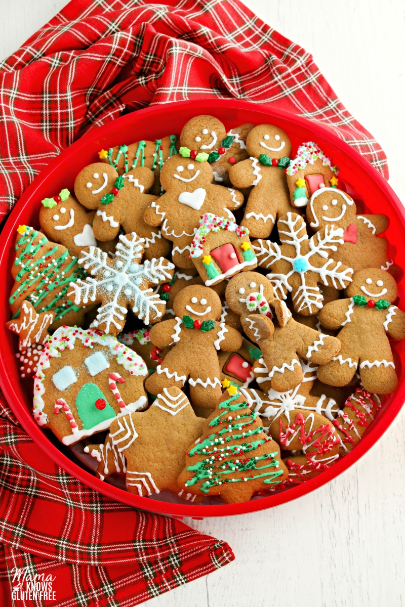 gluten-free gingerbread cookies in a rec cookie tin with a plaid napkin on a white surface