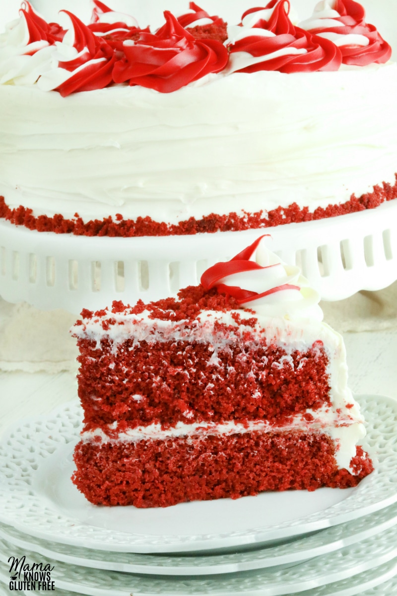 gluten-free red velvet cake slice on a white plate with the cake in the backgorund