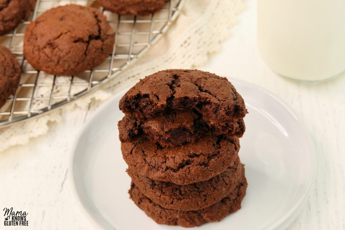 gluten-free chocolate cookies stacked on top of each other on a white plate with the cookies and milk in the background