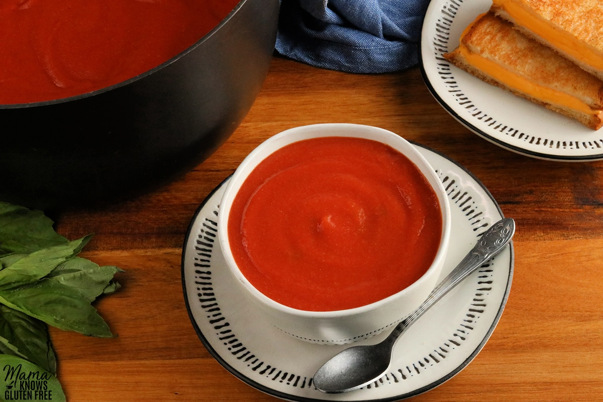 gluten-free tomato soup in a white bowl with grilled cheese sandwiches and the pot of soup, and fresh basil in the background