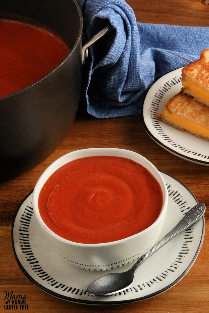 bowl of gluten-free tomato soup with a spoon and grilled cheese sandwiches and pot of soup in the back ground