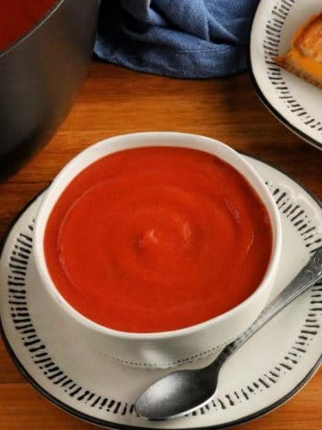 gluten-free tomato soup in a white bowl with a spoon, pot of soup and grilled cheese sandwich in the background