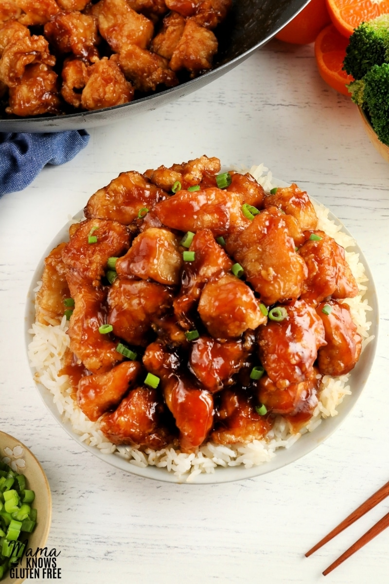 gluten-free orange chicken over rice in a white bowl with the wok of chicken, oranges, and broccoli, green onions and chopsticks in the background