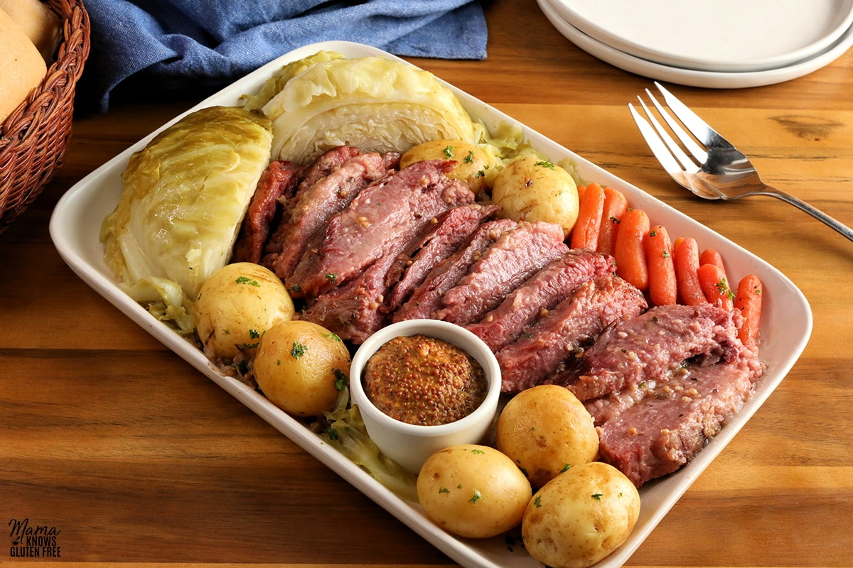 corned beef, cabbage, carrots, potatoes, and mustard on a white platter with plates, a fork and rolls in the background