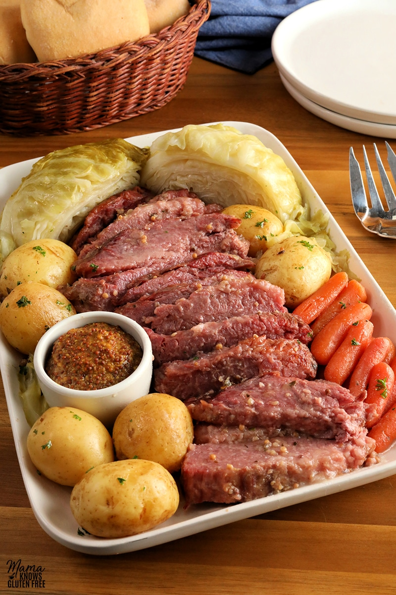 corned beef, cabbage, carrots, potatoes, ramikin of mustard on a white platter with a servign fork, white plates and basket of bread in the background