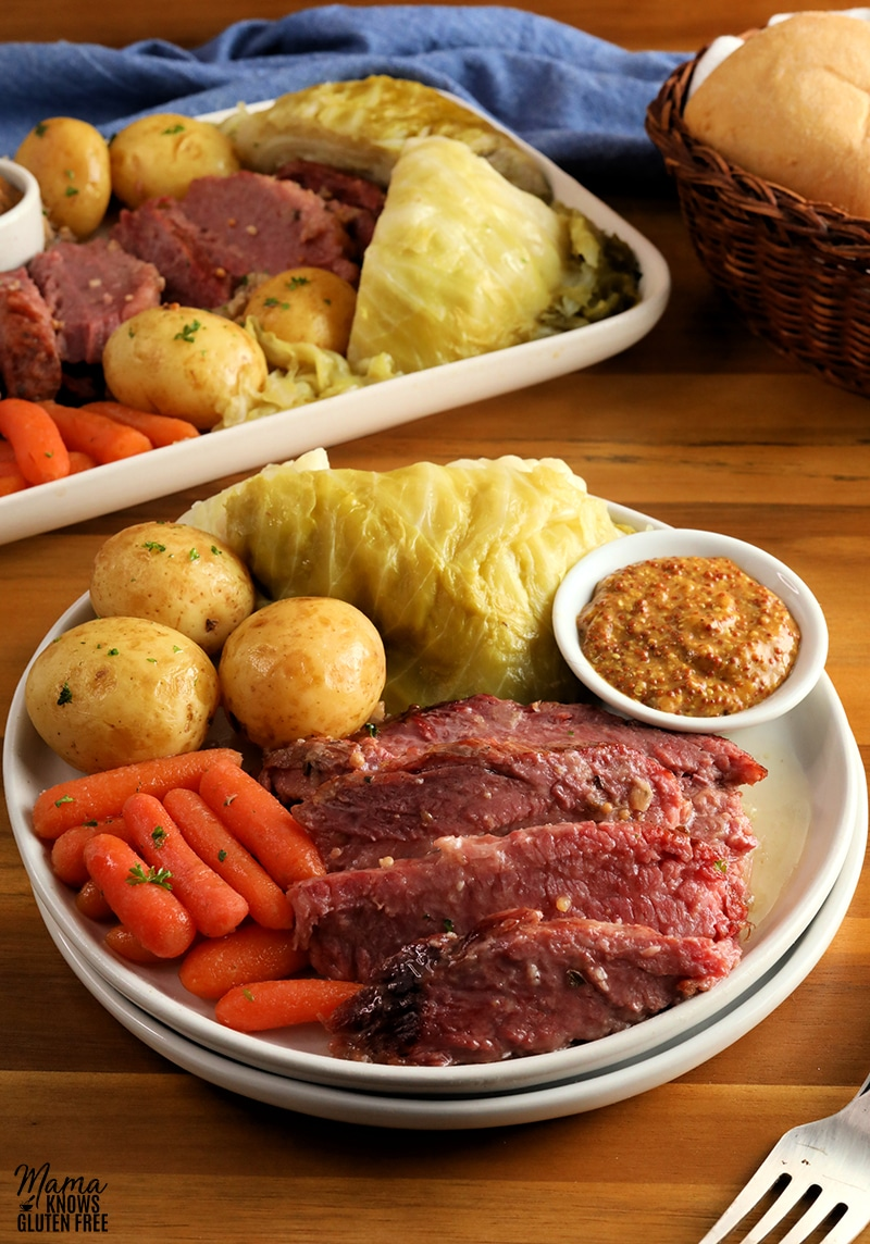 corned beef, cabbage, carrots, potatoes, mustard on a white plate with a fork, with a platter and basket of bread in the background