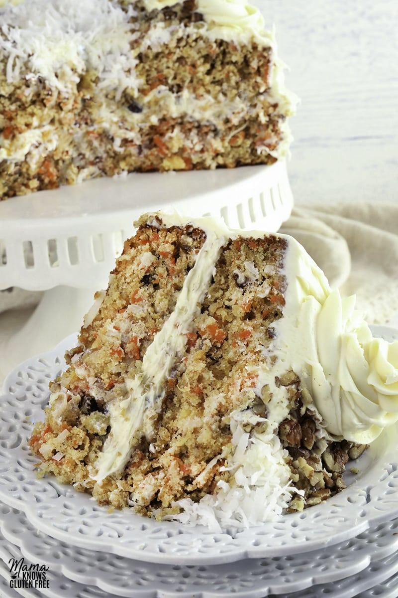 gluten-free carrot cake slice on a white plate with the cake on a white cake stand in the background