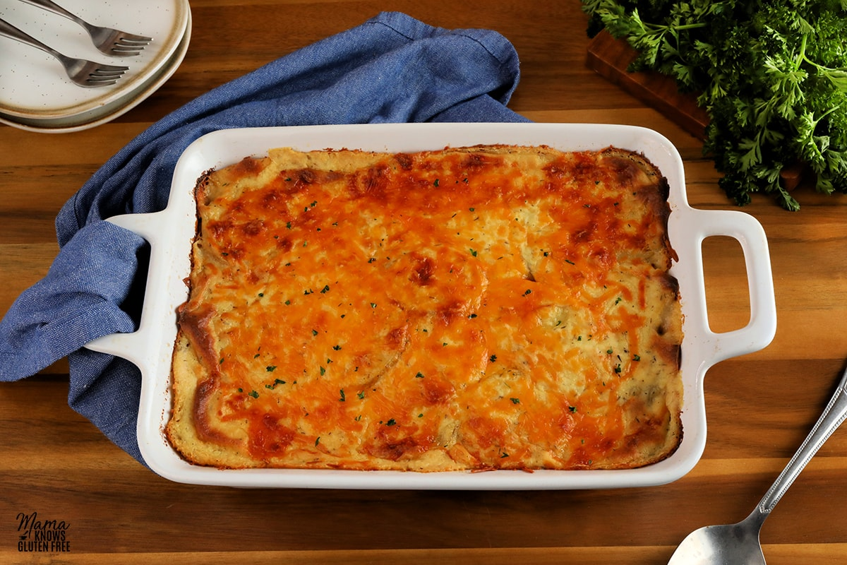 gluten-free scalloped potatoes in a white baking dish with white plates, forks, a blue napkin, parsley and serving spoon