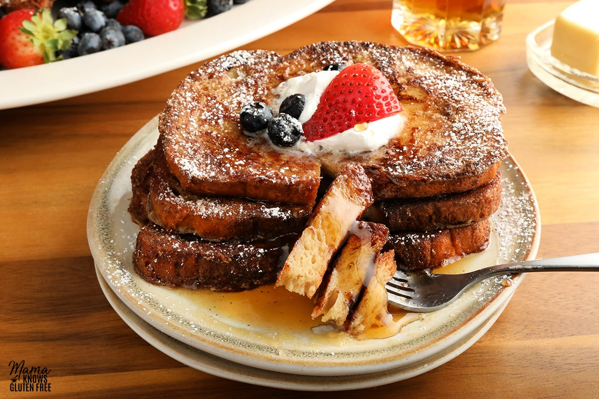 gluten-free French Toast topped with whipped cream, berries and syrup on a white plate with a fork with butter, syrup and platter of French toast and berries in the background