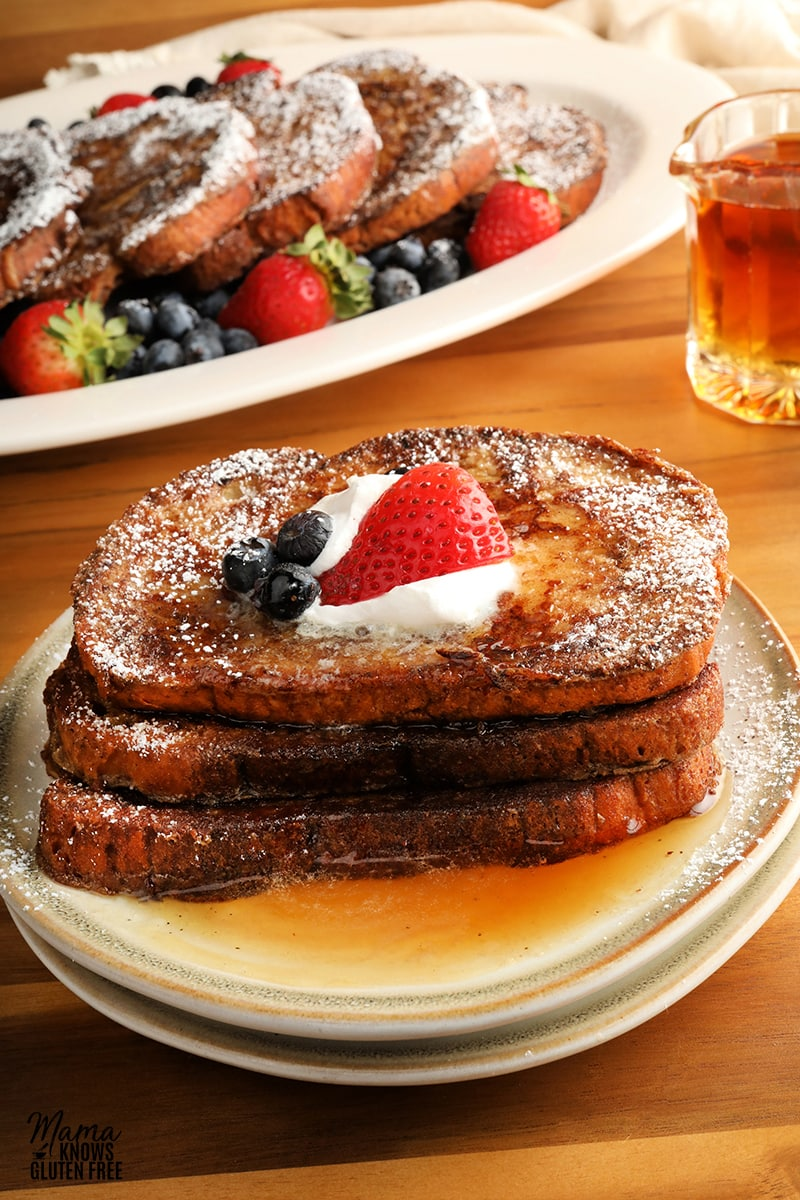 three pieces of gluten-free French Toast slices topped with berries, whipped cream, and syrup on a white plate with a platter for French Toast and syrup in the background
