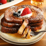 gluten-free French Toast topped with berries, whipped cream, and syrup on a white plate with a fork