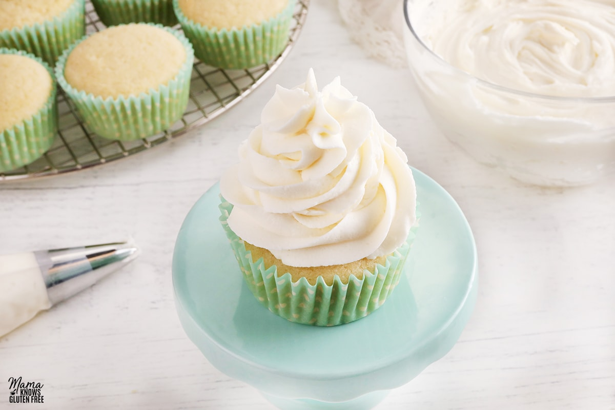 gluten-free vanilla buttercream frosting on a vanilla cupcakes with the frosting and cupcakes in the background